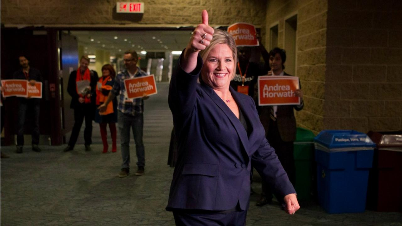 Andrea Horwath smiles and gives a thumbs up as supporters hold signs in the background.