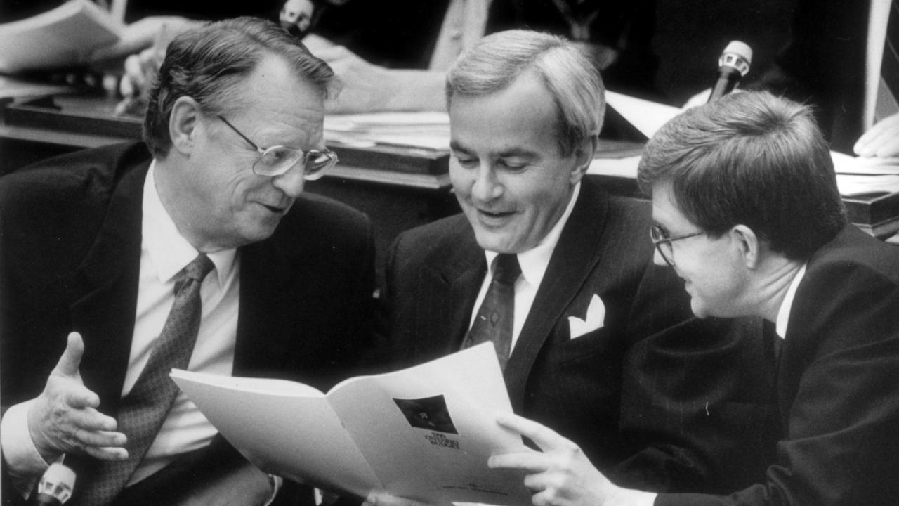 Man looks at document, flanked by two other men.