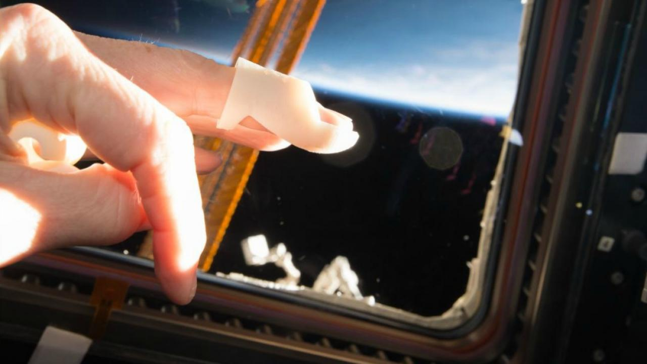 demonstration of 3D printing with a hand touching a screen