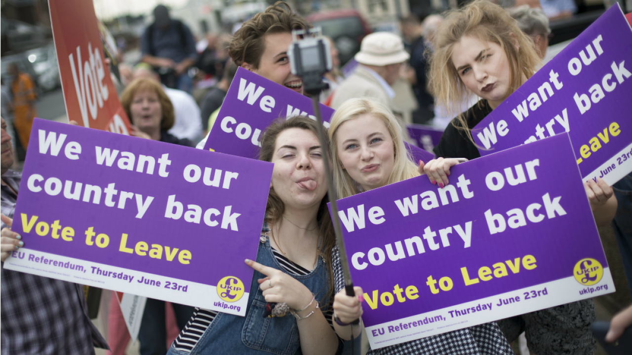 young adults holding purple signs in support of brexit