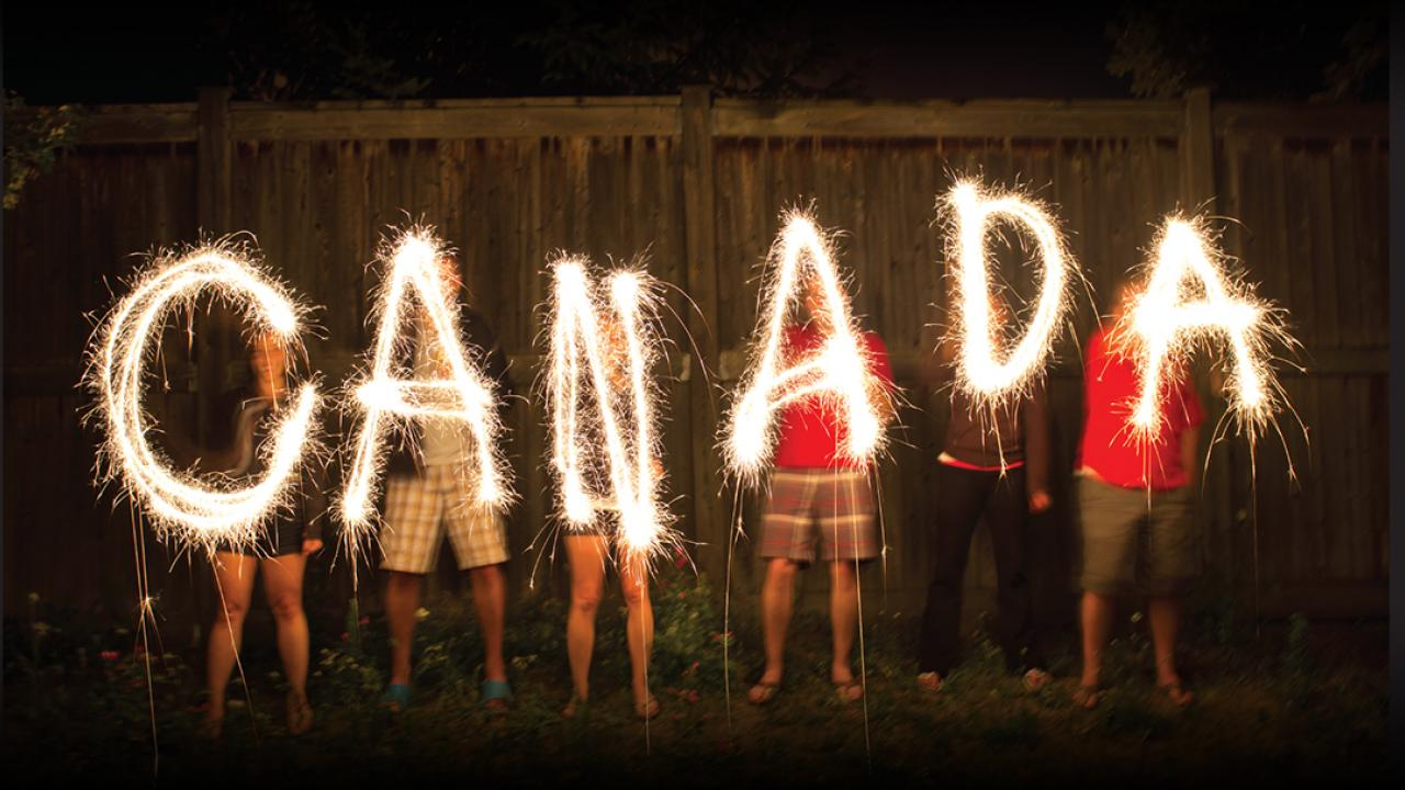 Six people spell out CANADA with sparklers.