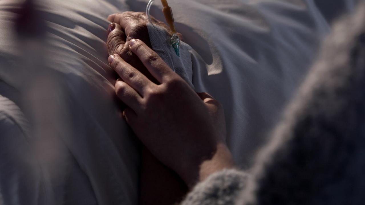A person lying on a hospital bed with an IV has their hand held by a relative.