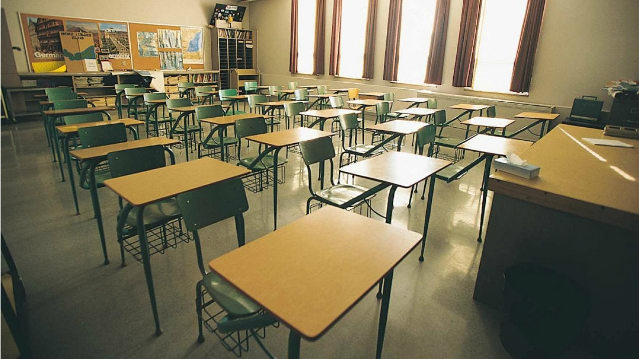 Rows of desks in empty classroom.