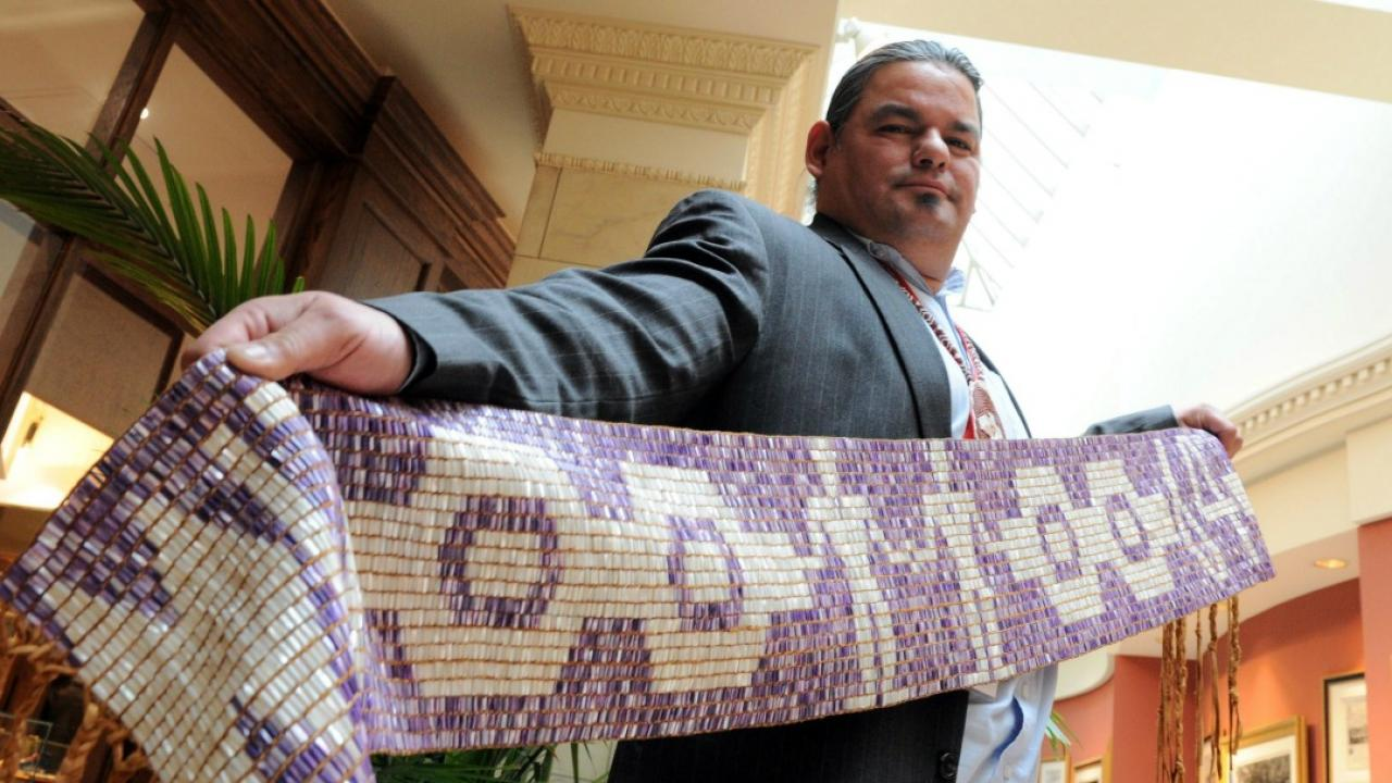 Ontario Chief Isadore Day holds a purple and white beaded wampum belt.