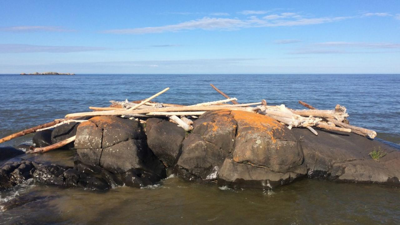A pile of sticks and rocks on the shore of Lake Superior