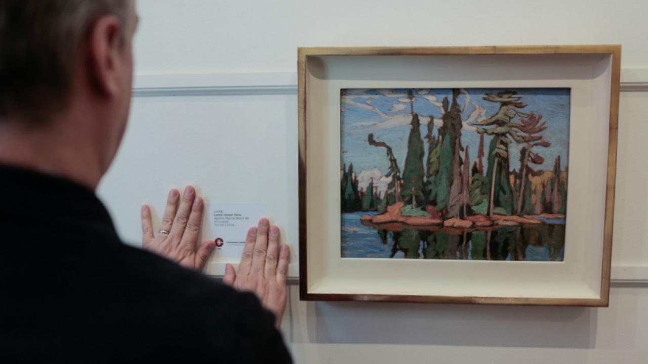 Artist Lawren Harris's Algoma Sketch 48 being hung at a gallery