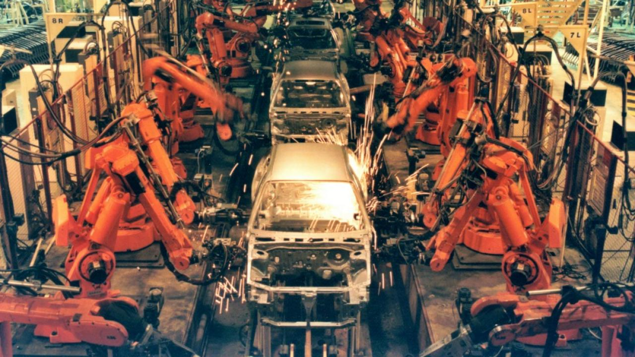 Robotic arms weld car chassis together on an assembly line.