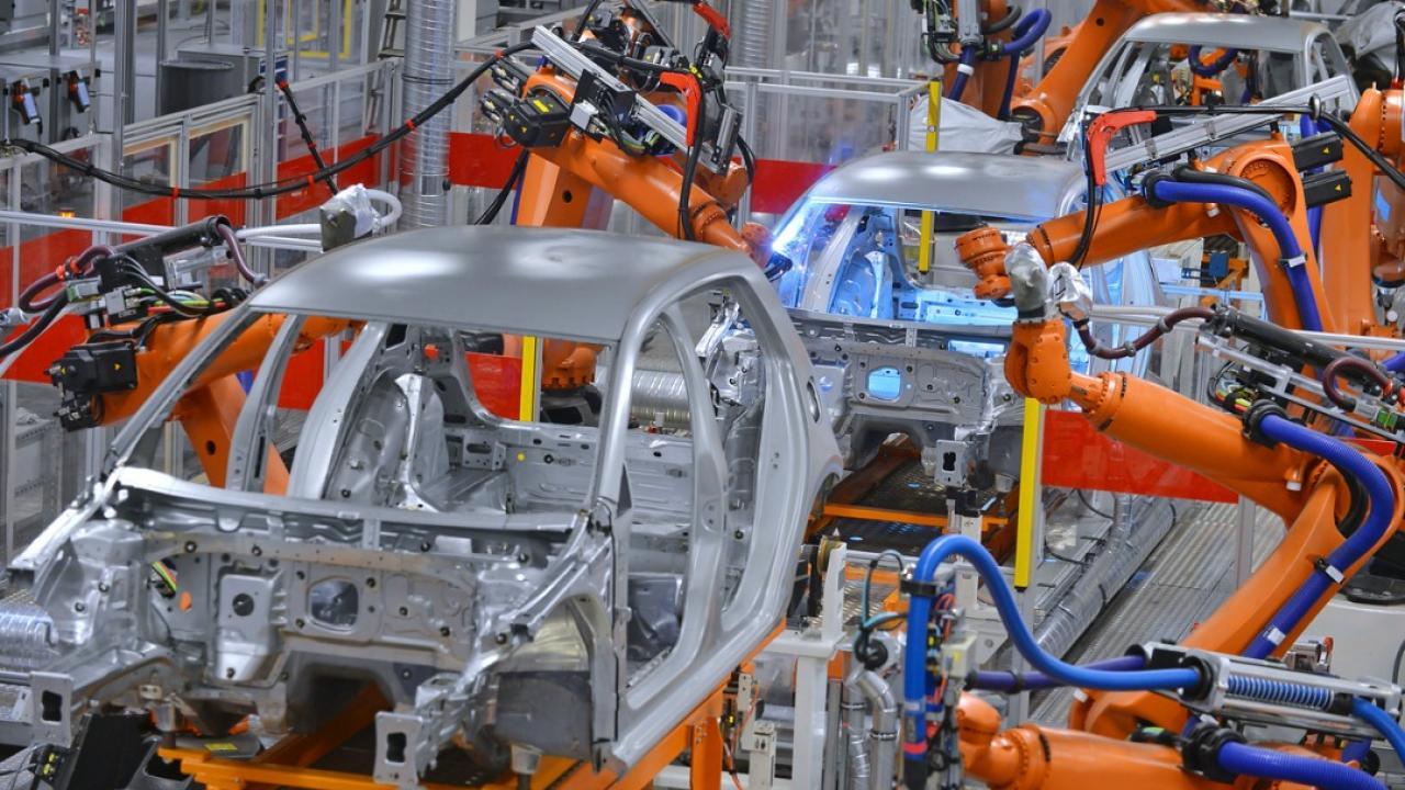 Robot arms assemble cars.