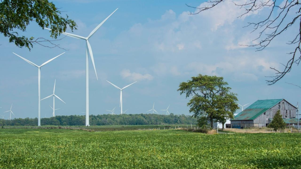 Wind turbines stand next to a farm.
