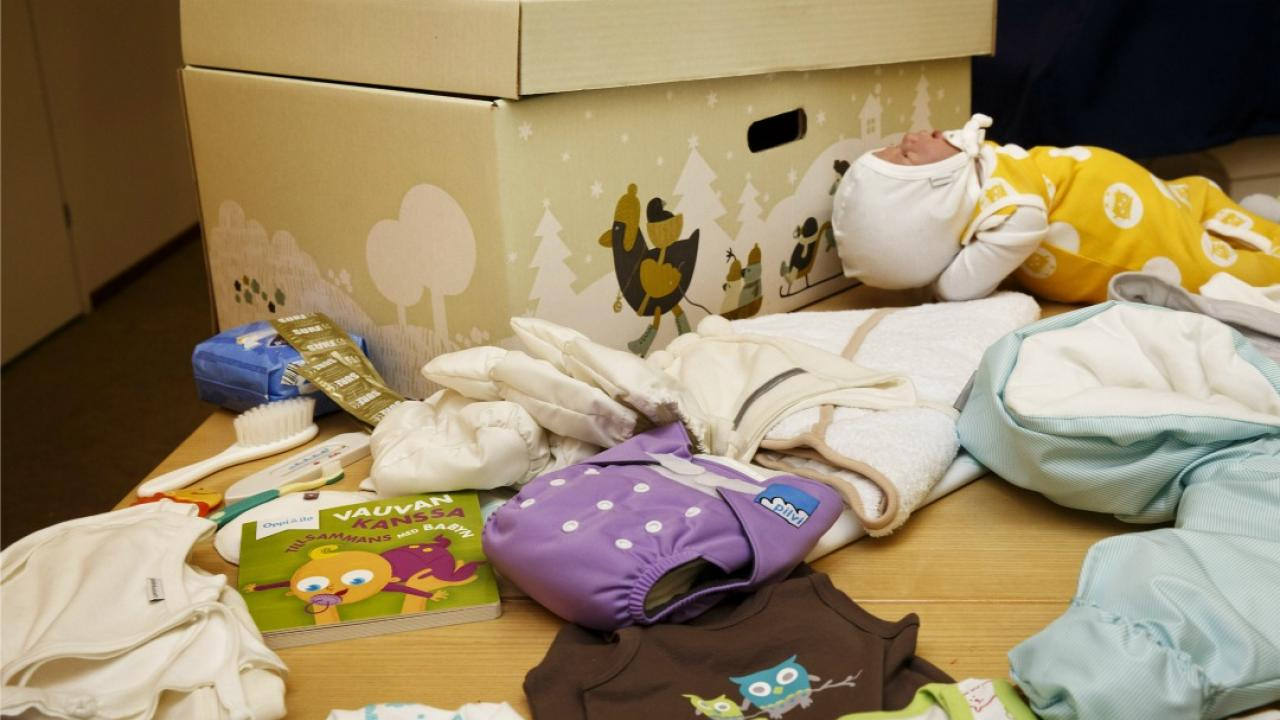 a box full of essentials for newborns such as clothing and diapers