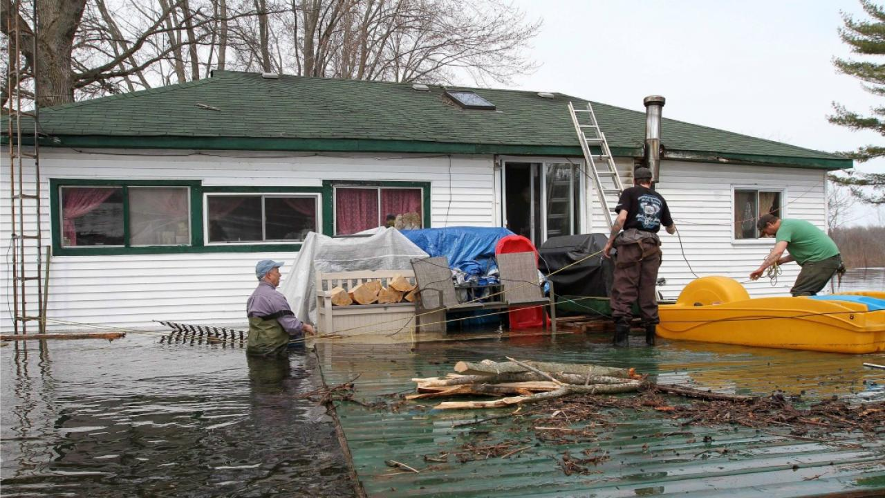 people wading in flood water to tend to a partially immersed house