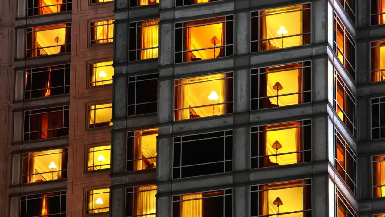 Illuminated windows shine from a condo building at dusk.