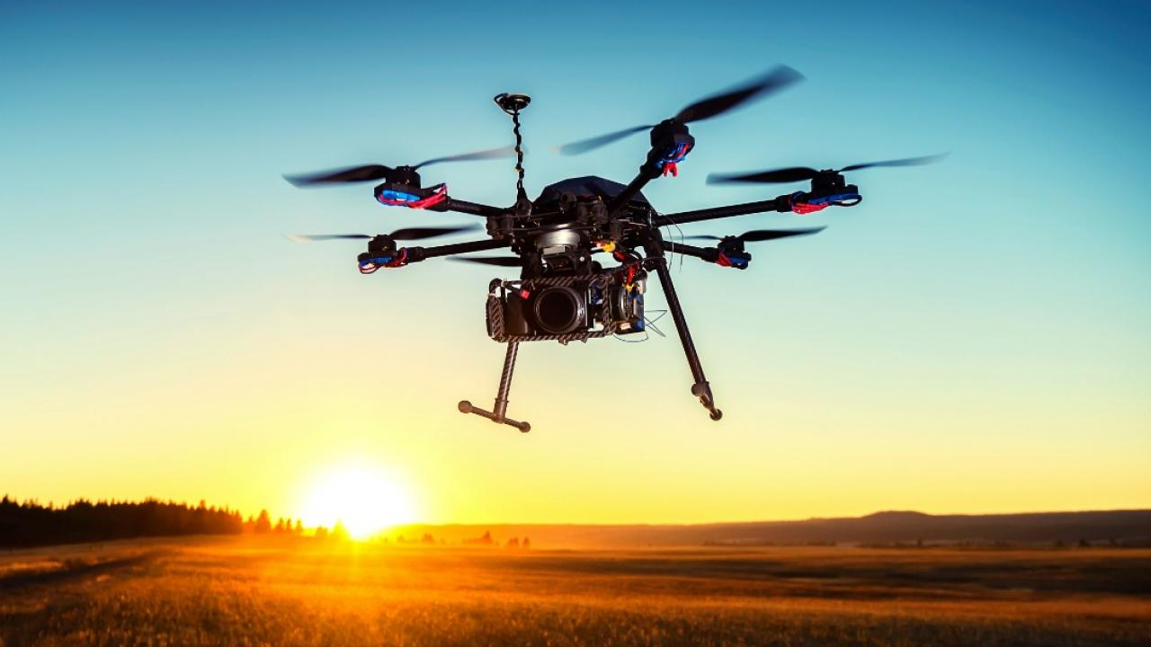 a drone flying over a field at sunset