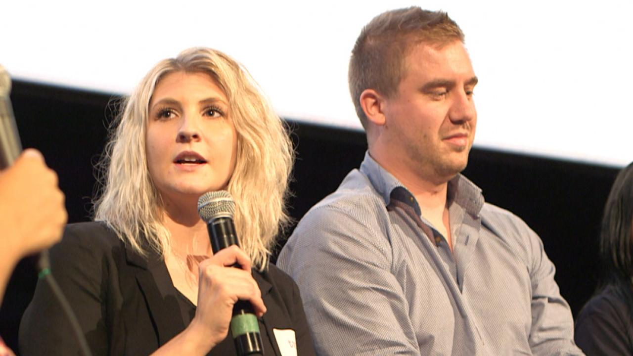 two young people speaking on stage