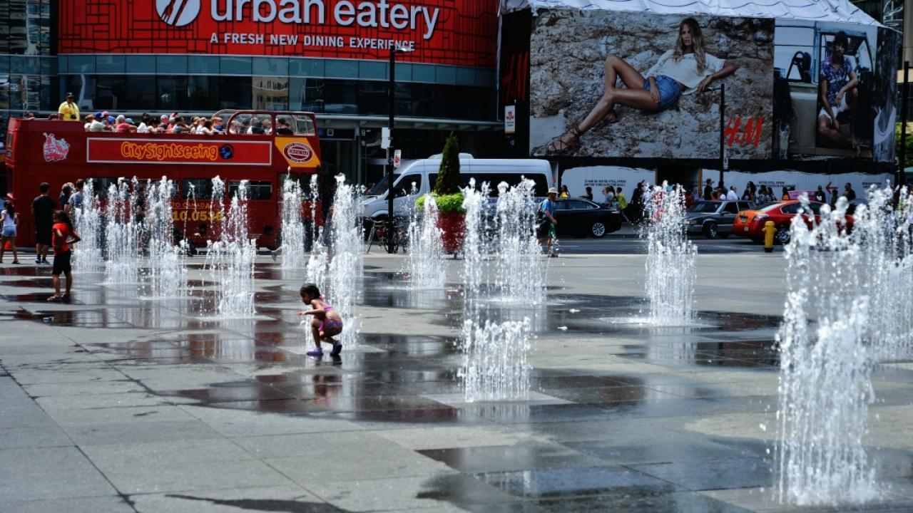a child runs through a city fountain during a heat wave