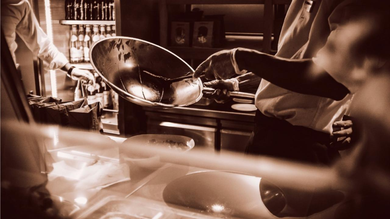 a cook making food in a restaurant kitchen