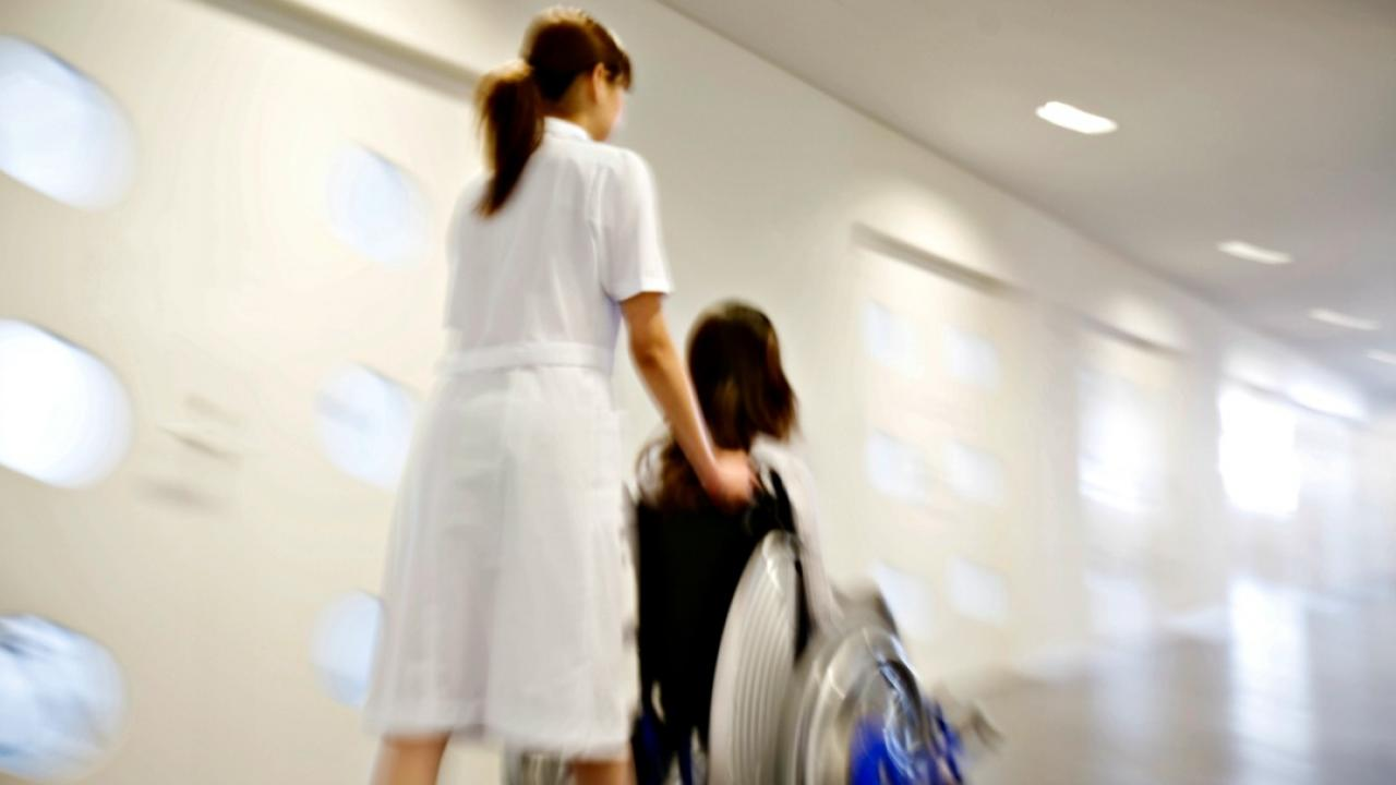 nurse pushing patient in a wheelchair down the hall
