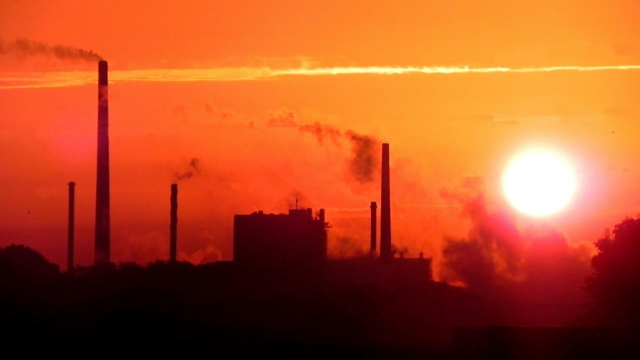 Smokestacks with orange sky in background.