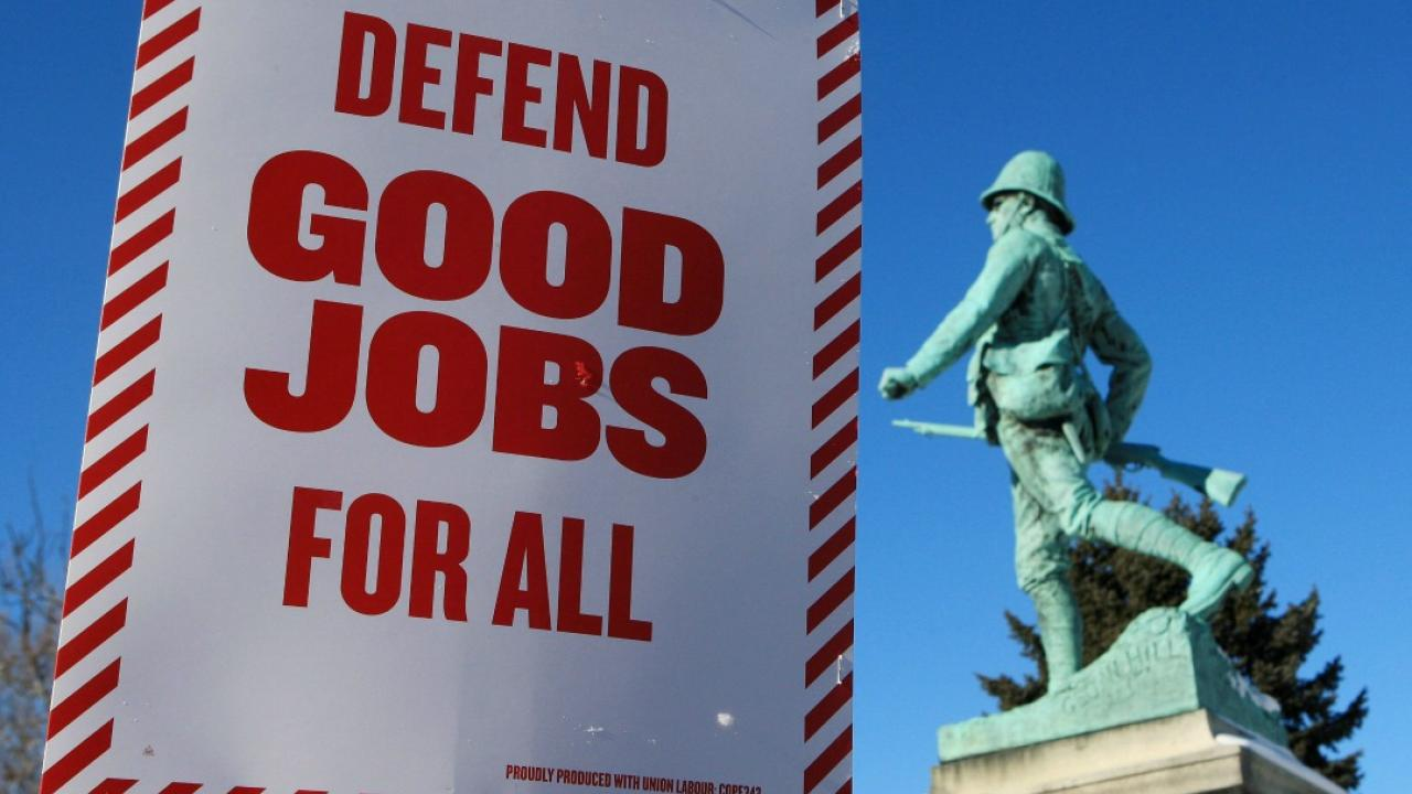 """a sign that says, """"defend good jobs for all"""""""