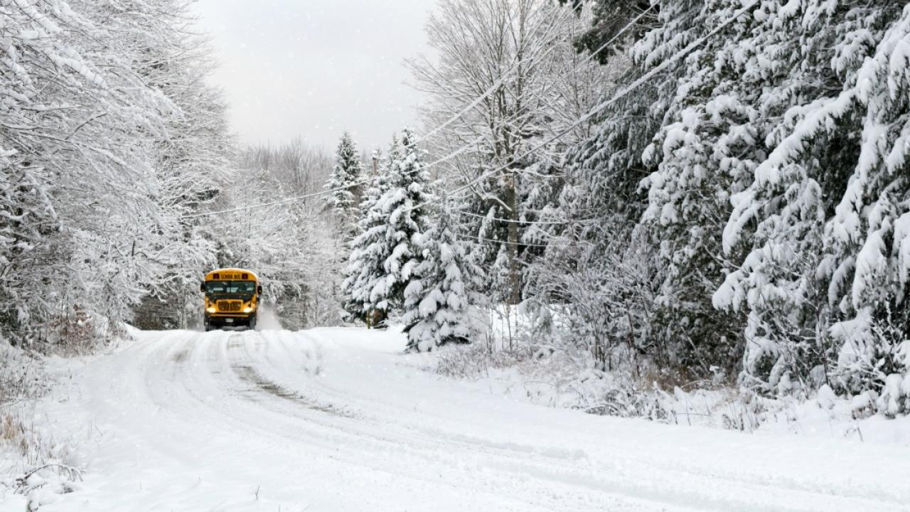 school bus driving on a snowy rural road