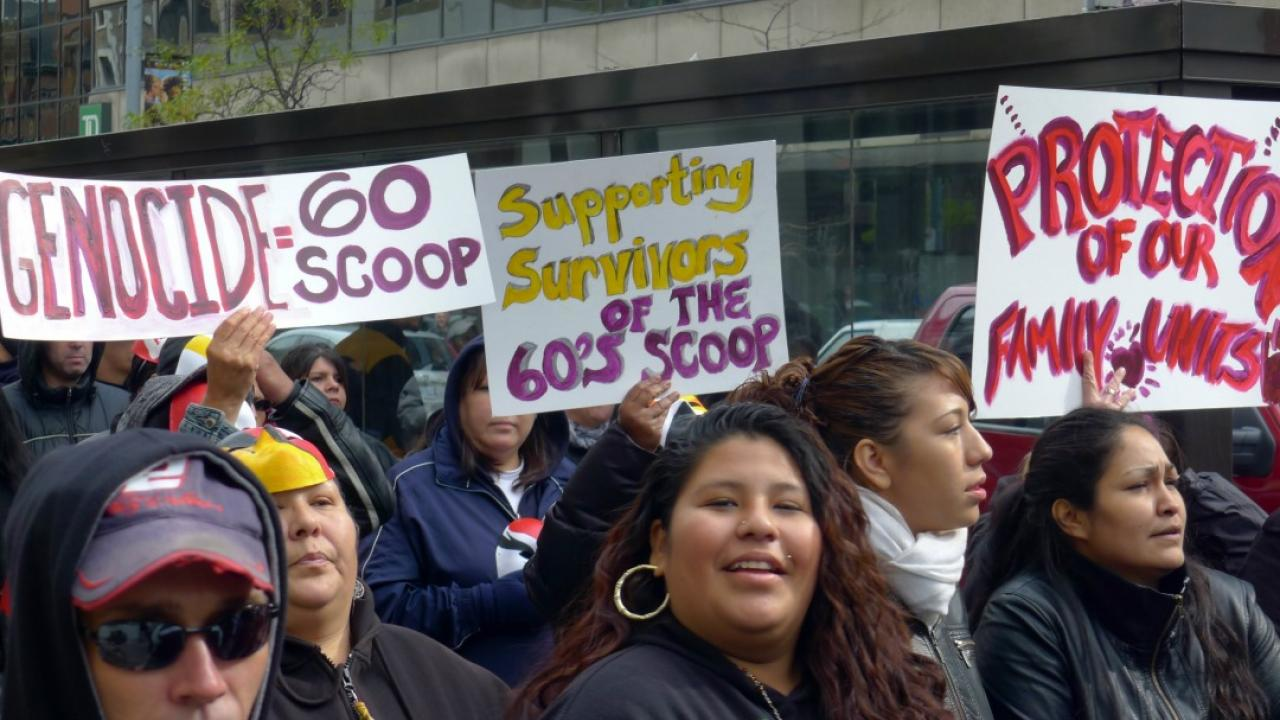 a group of people protesting the sixties scoop in Canada