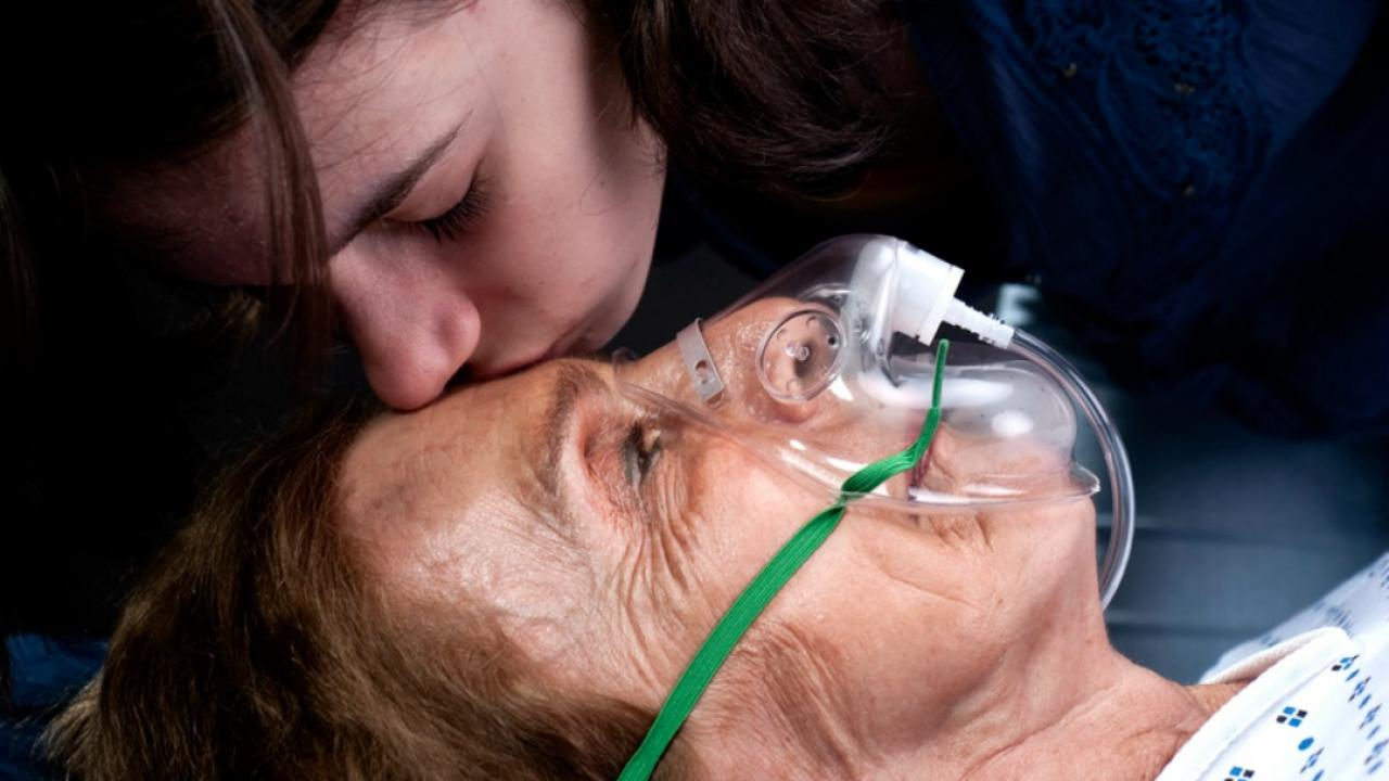 a woman with an oxygen mask and a teen girl kissing her forehead