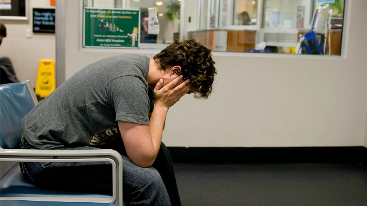 a young man with head in hands in a hospital waiting room