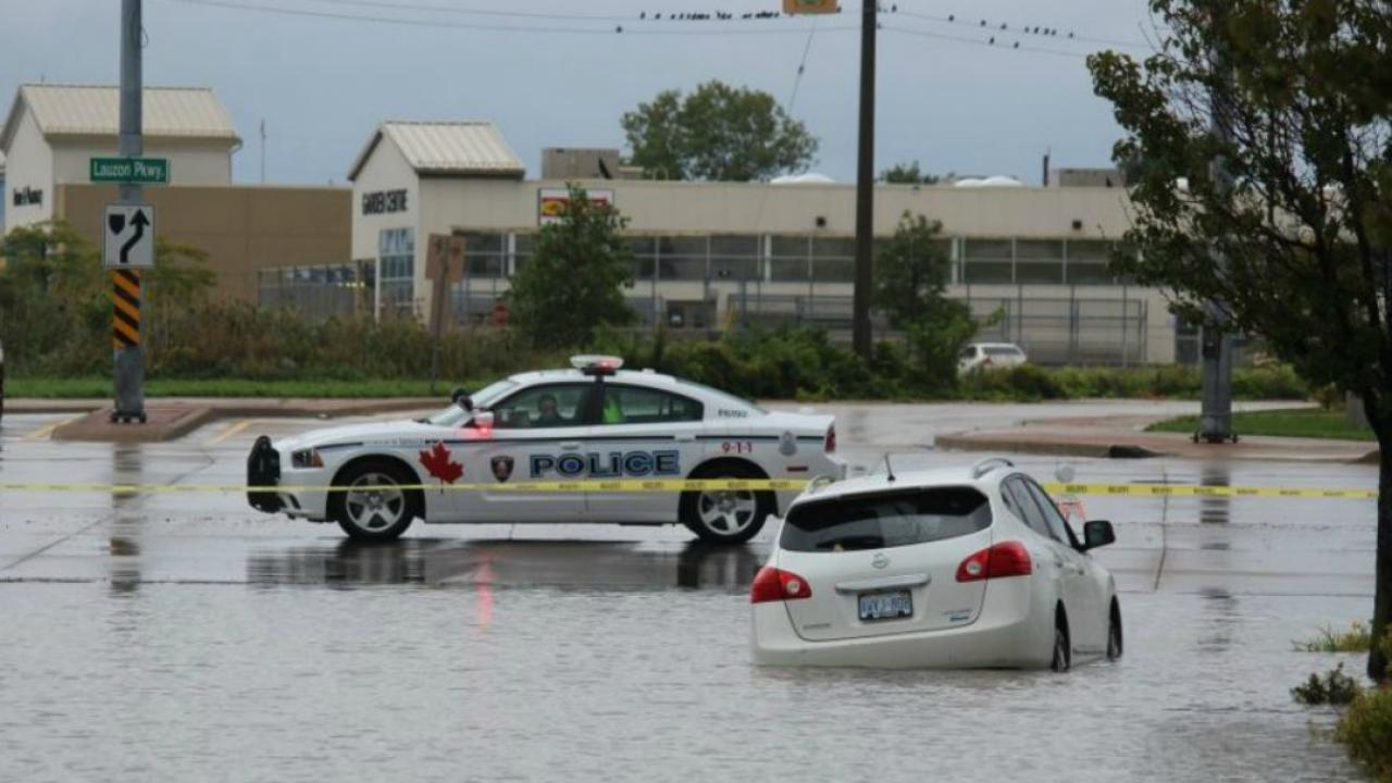 a car and police car immersed in a flooded street