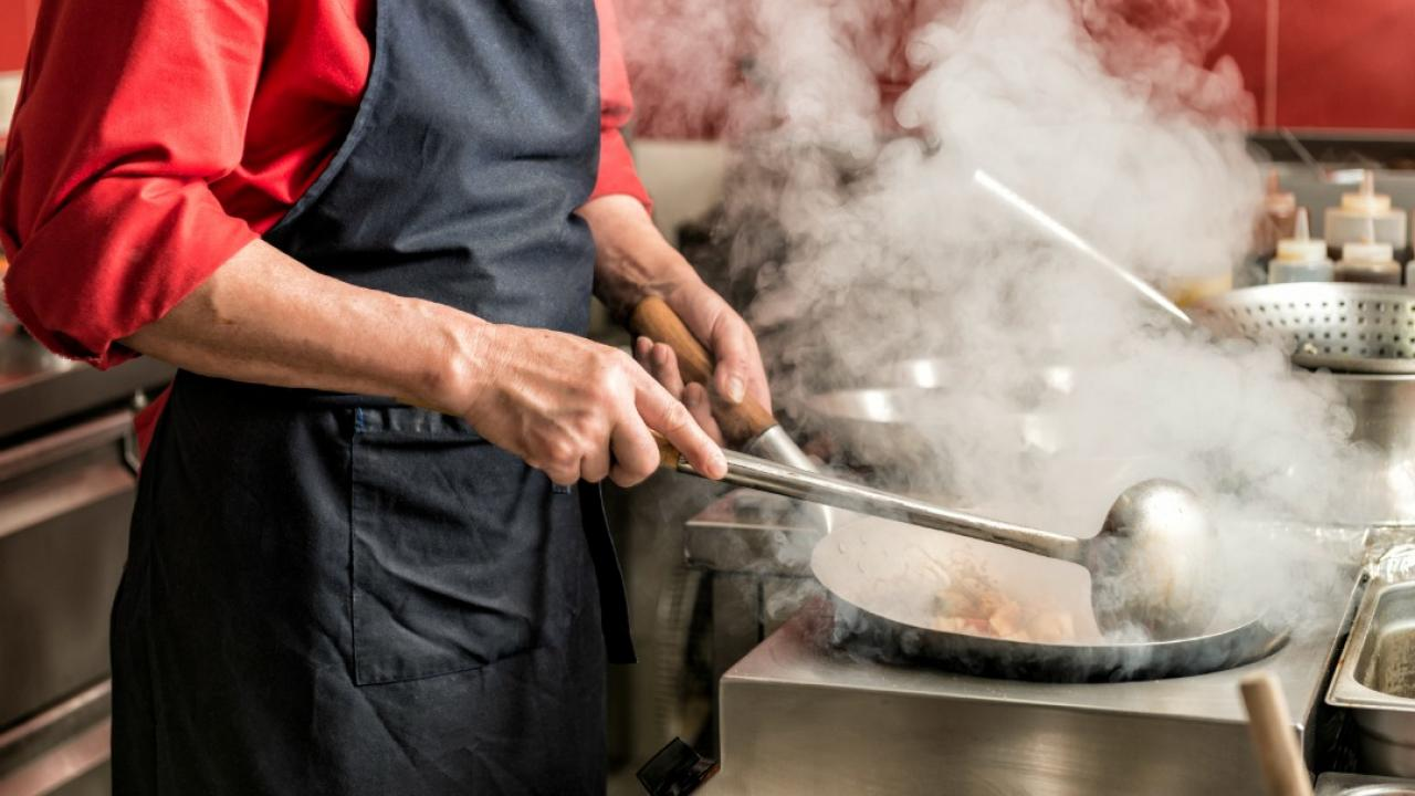 person in a restaurant kitchen using a wok