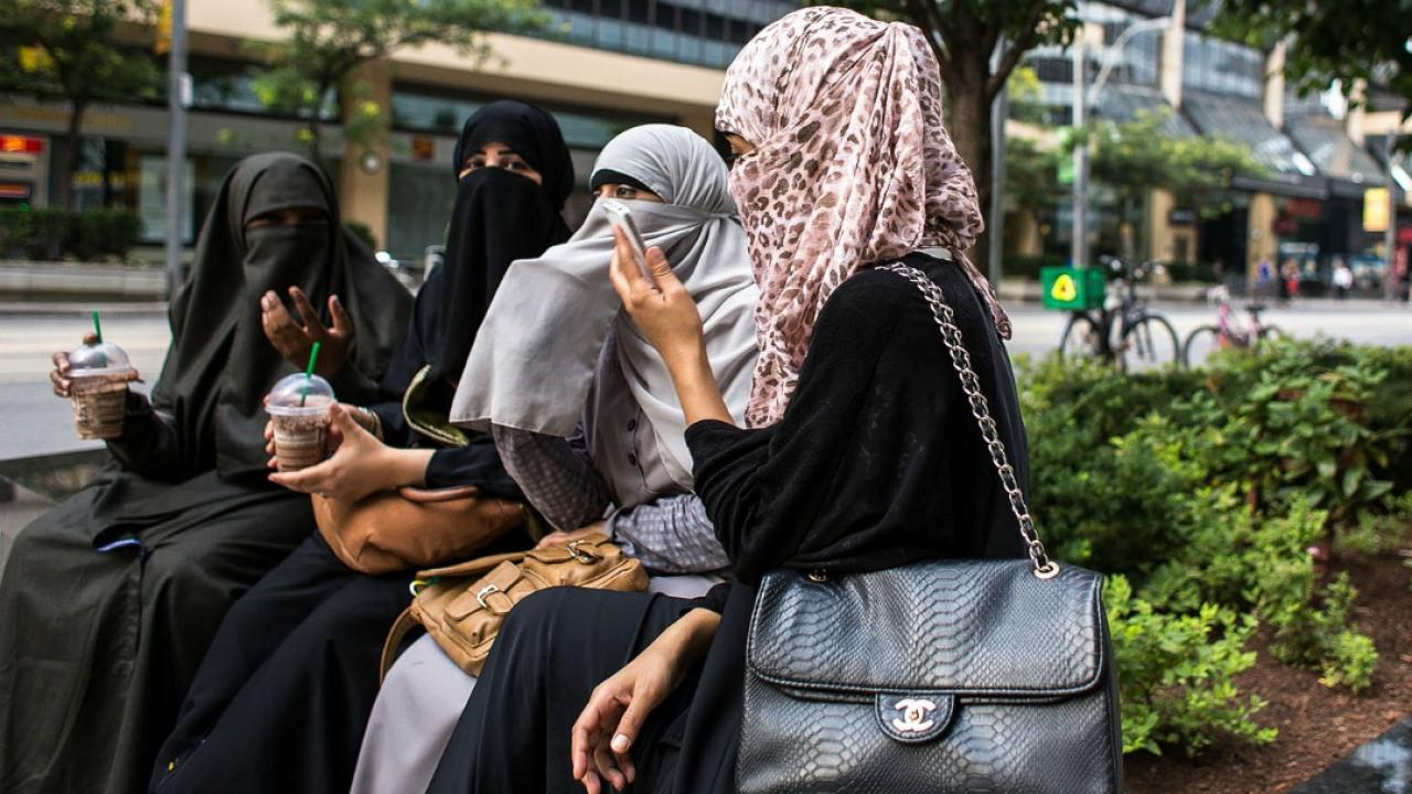 four women in niqabs sipping coffee