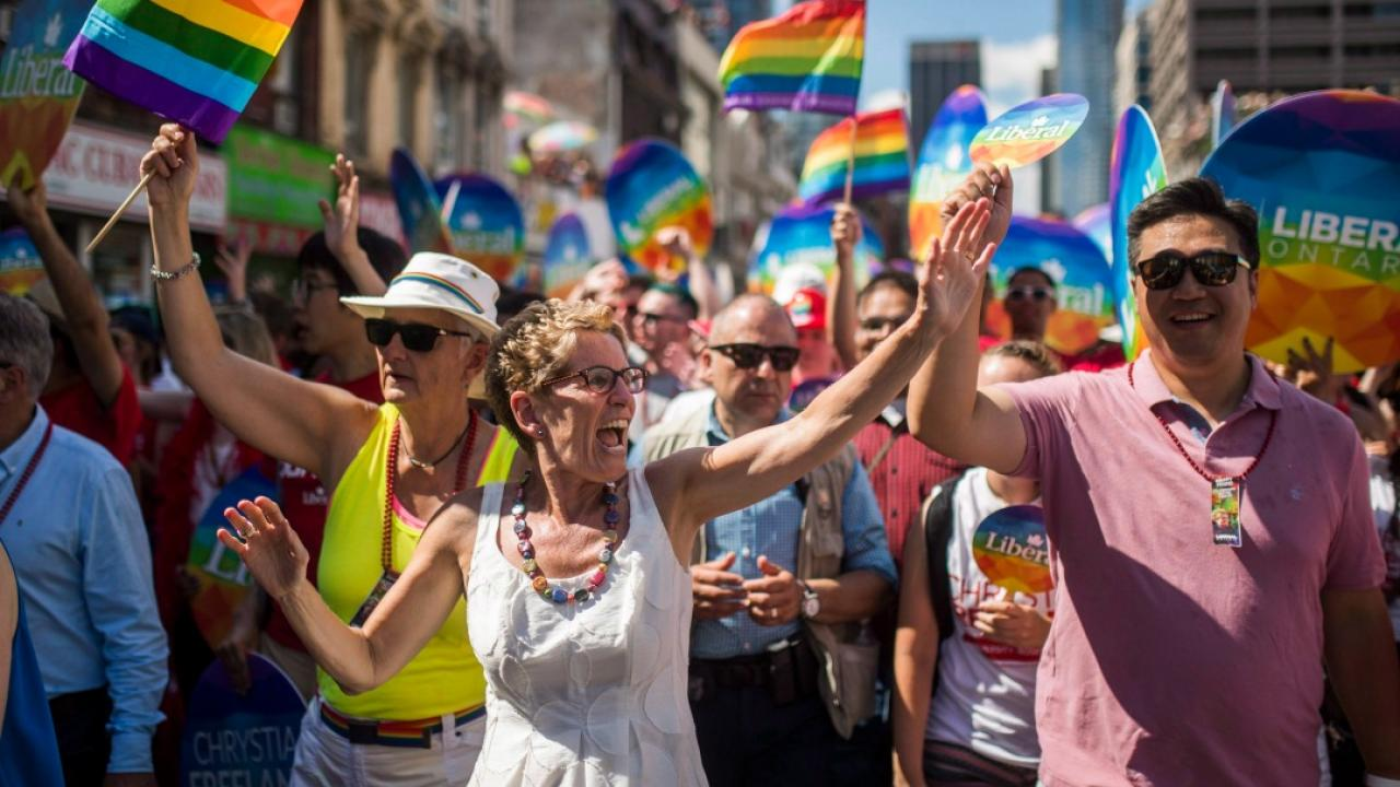 Kathleen Wynne waving to crowd at the Pride Parade in Toronto