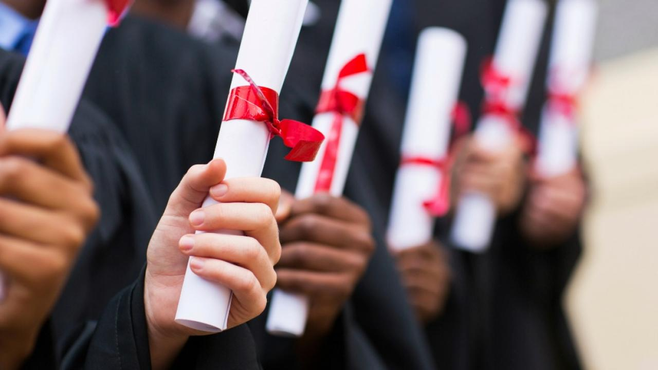 students holding college diplomas
