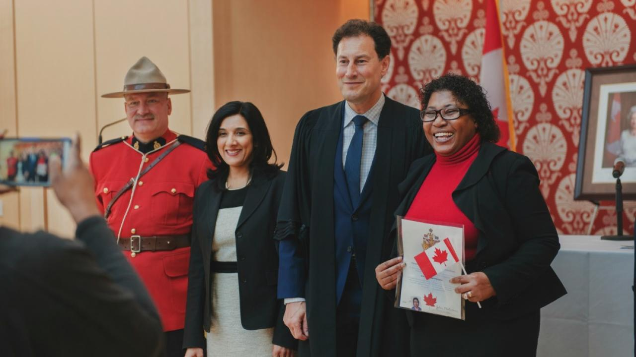 TVO host Steve Paikin with three people at a citizenship ceremony