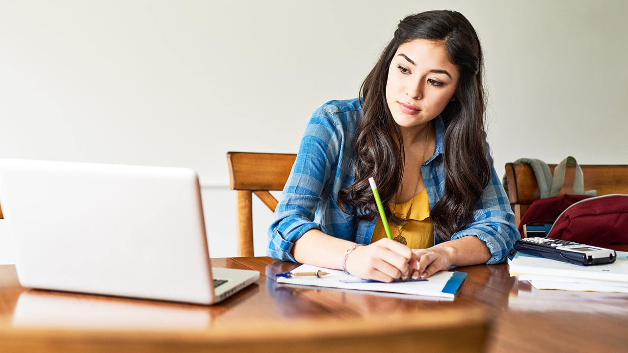 Woman at desk taking notes while looking at laptop.