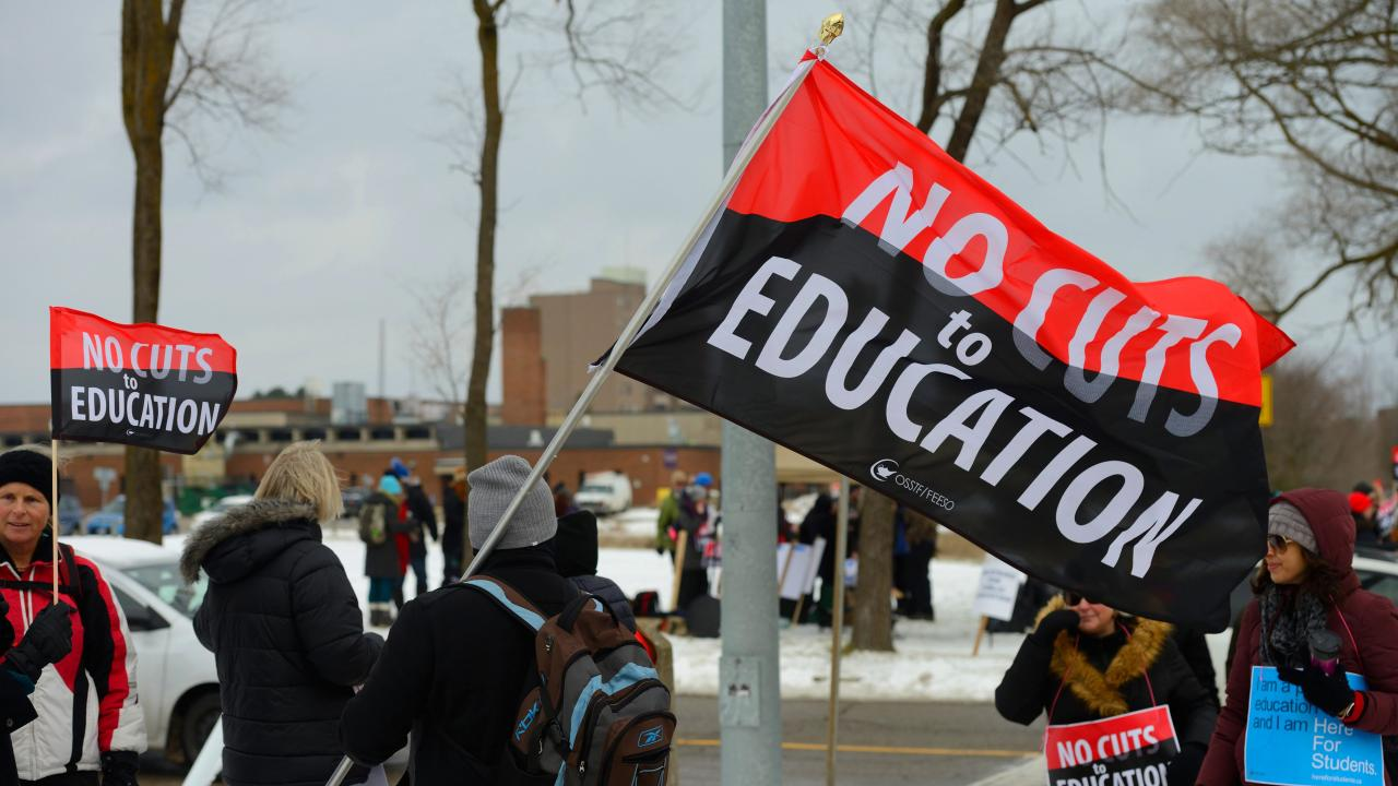 "Banner at protest reads ""No cuts to education"""