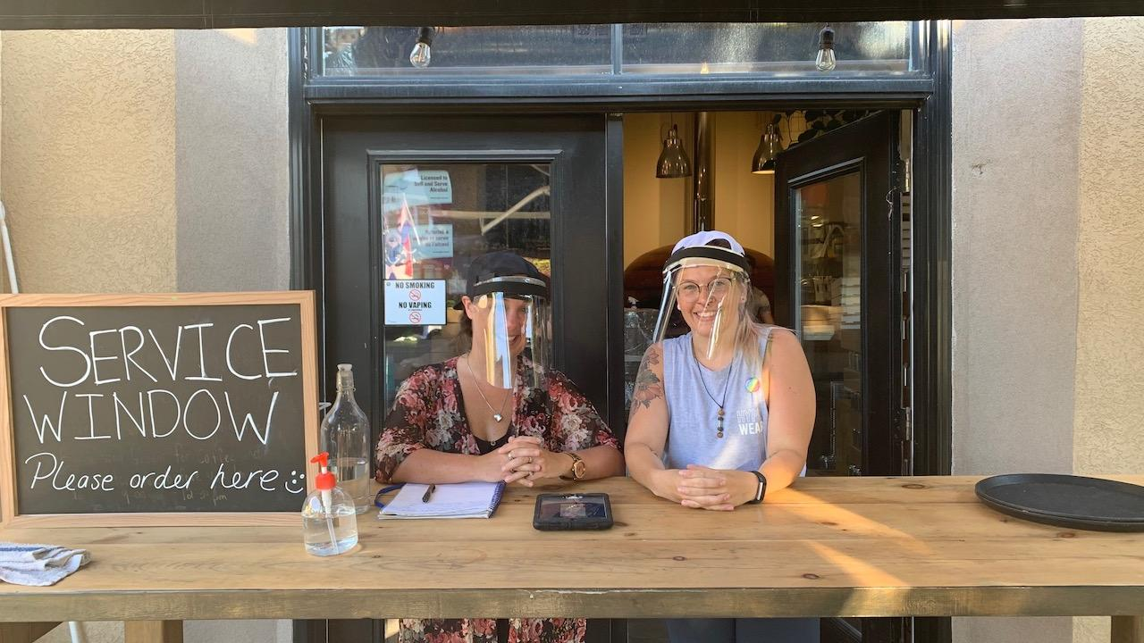 Two women wear face shields outside a restaurant