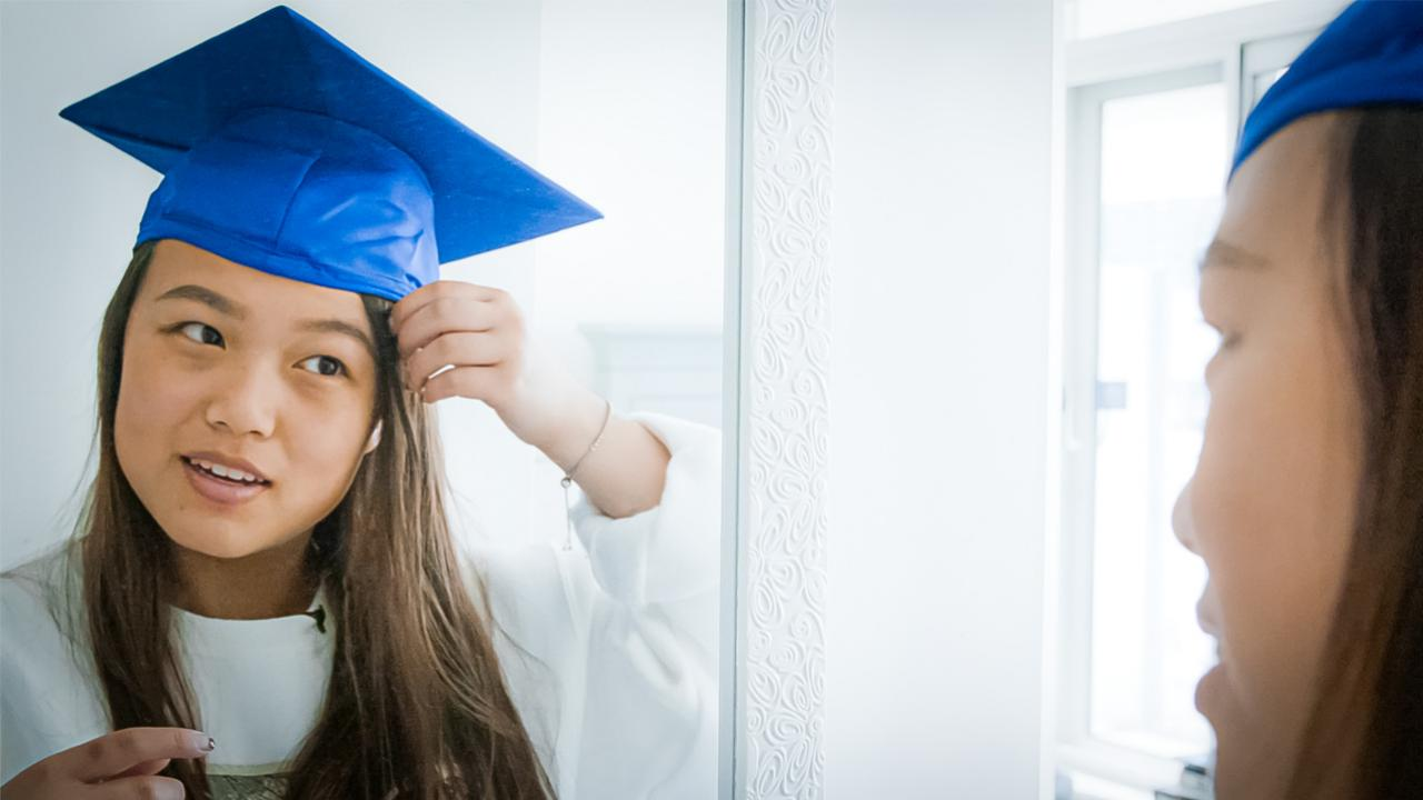 Young woman looking in mirror wearing a graduation cap