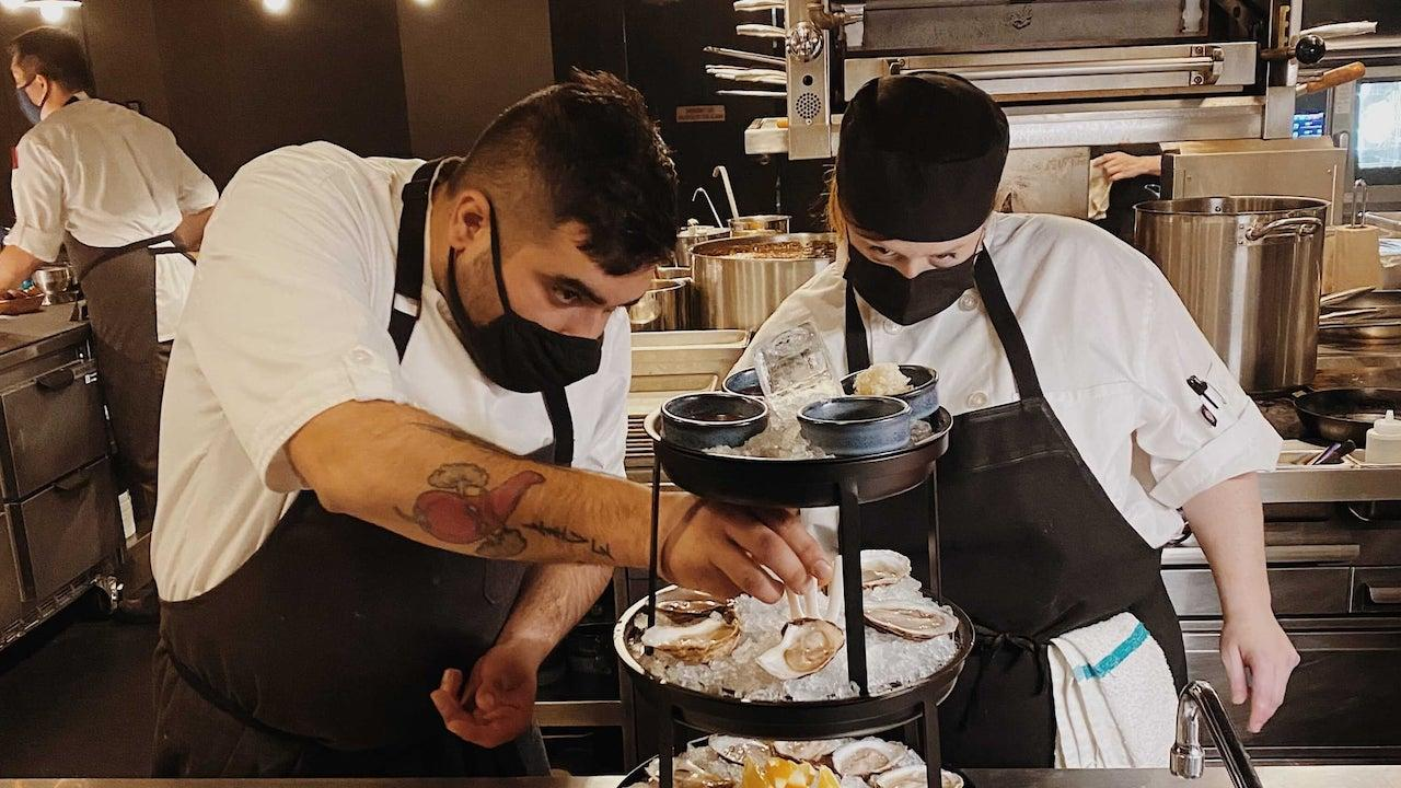 two masked men bend over plates of oysters