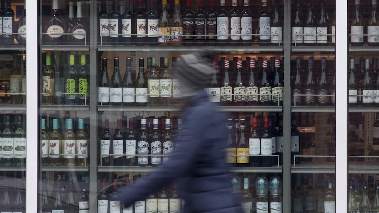 out-of-focus person walks past rows of wine bottles