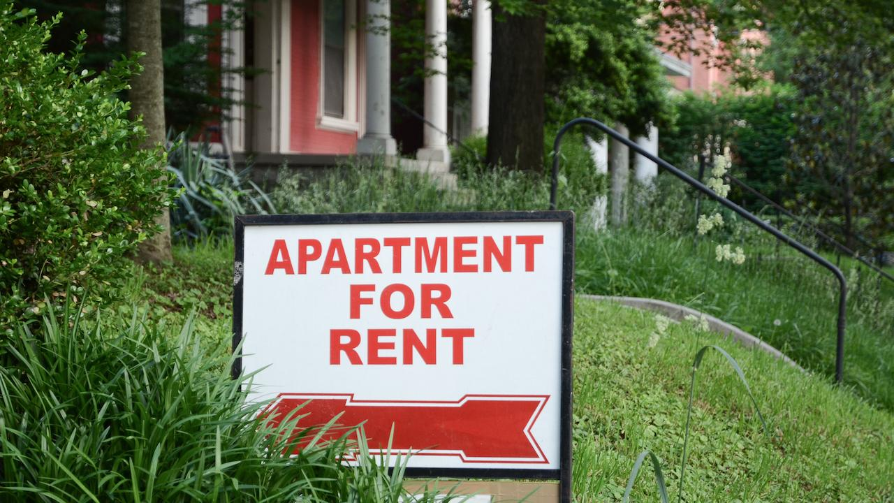 """an """"apartment for rent"""" sign on a lawn outside a house"""