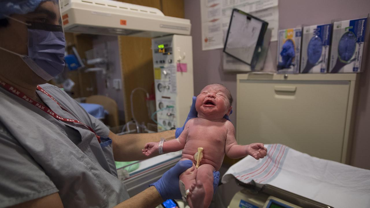 masked health-care worker holds up a newborn baby