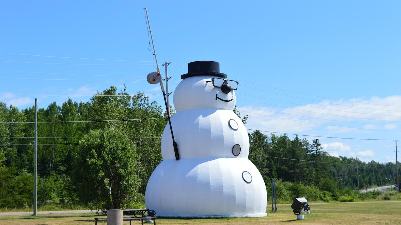 a giant snowman with a top hat and fishing rod