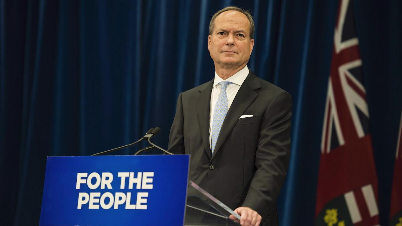 "suit-wearing man stands in front of a flag and behind a podium reading ""for the people"""