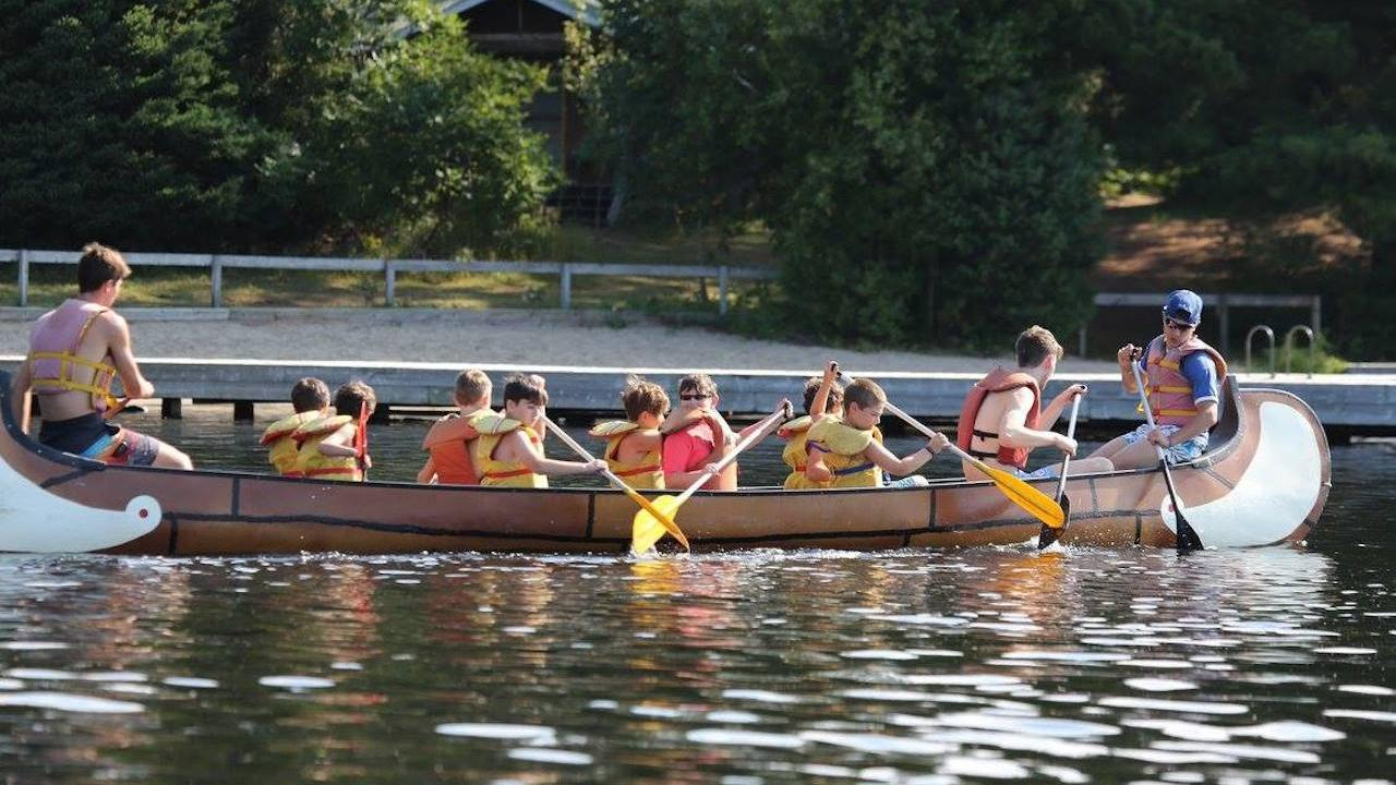 two adults and a group of children canoeing on a lake