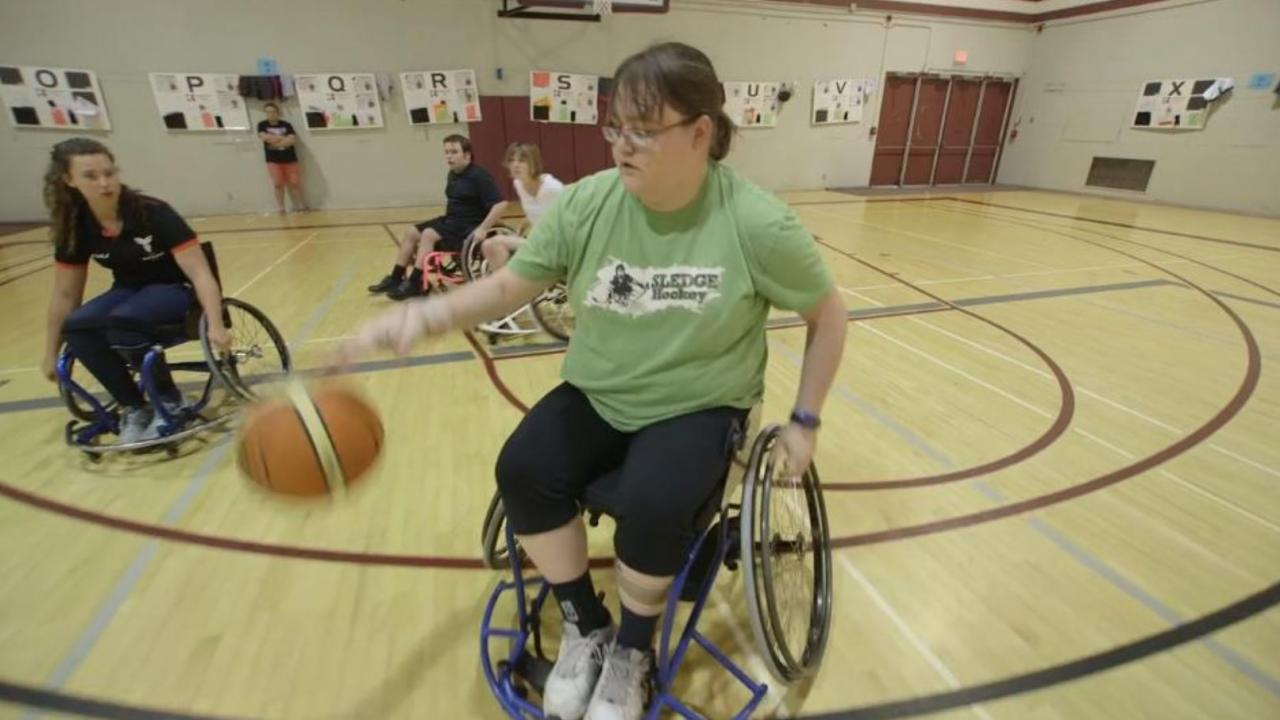 Woman in wheelchair bounces basketball.