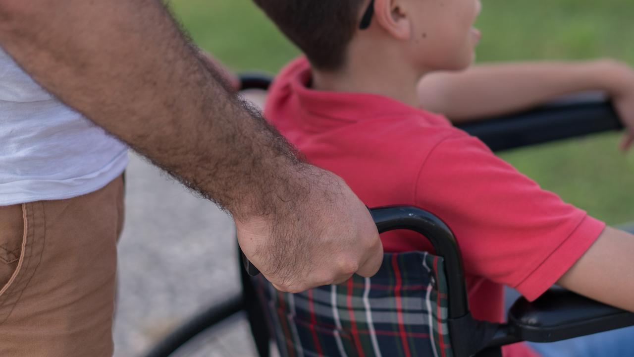 man pushing child in wheelchair