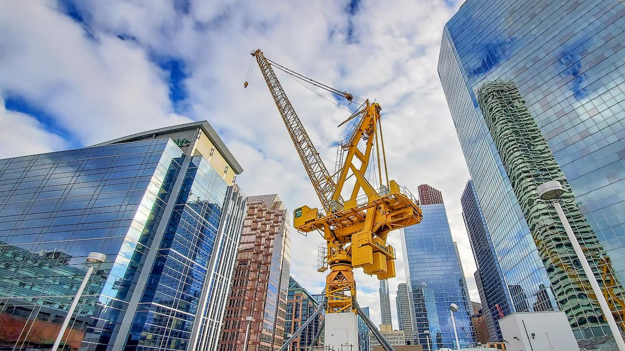a crane against a backdrop of condos