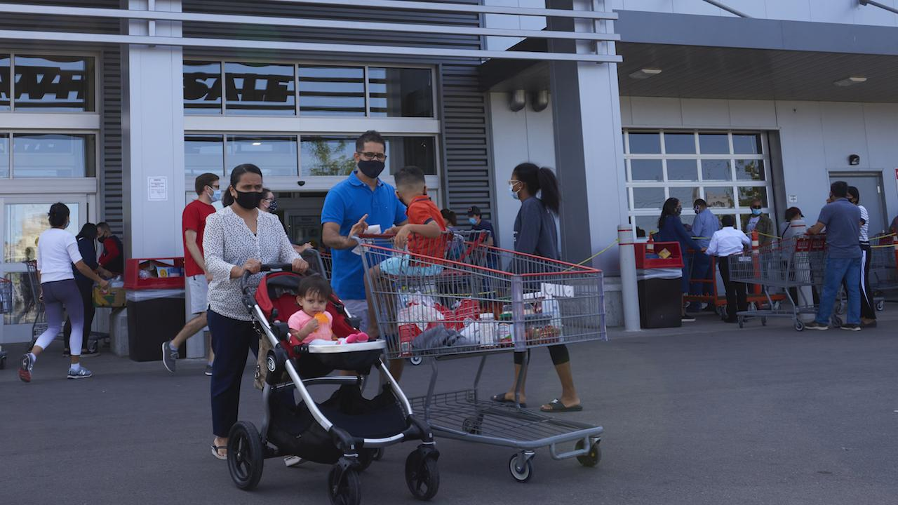 masked shoppers with a shopping cart outside a store