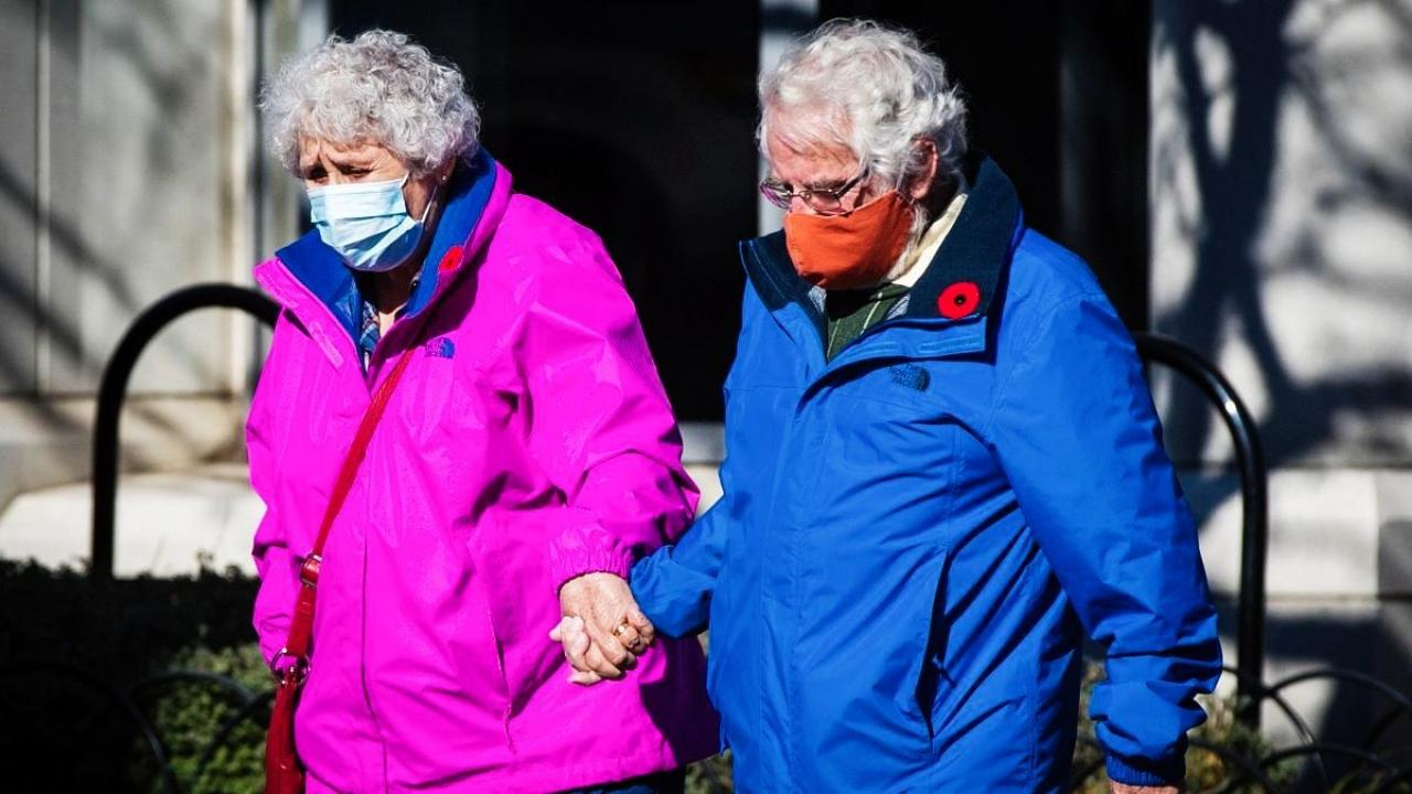 Elderly couple walks outside, holding hands while wearing masks.