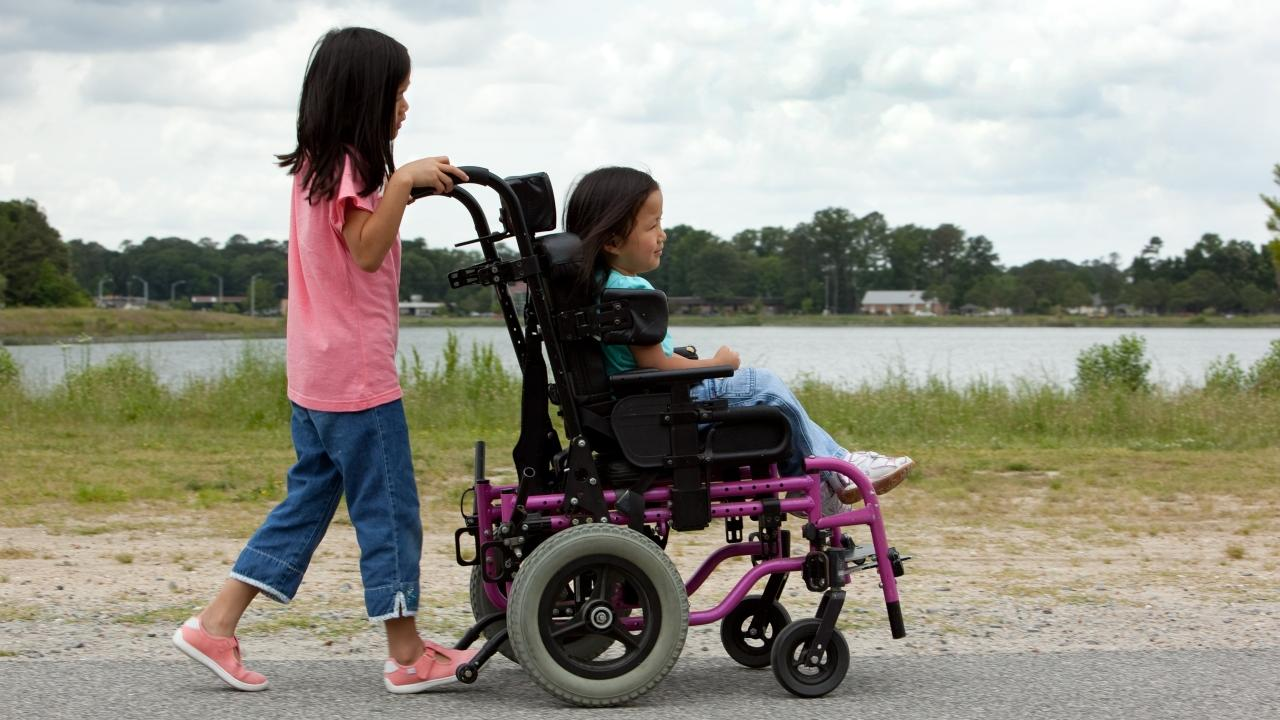 a child pushing another using a wheelchair